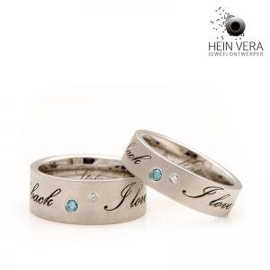 Tekstringen in edelstaal of RVS. Het blauwe diamantje stelt de aarde voor en het witte de maan. Door Hein Vera.